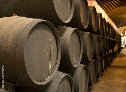 Obraz na plátně Row of stacked wooden wine barrels for sherry aging