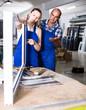 Leinwandbild Motiv Foreman explaining plastic windows assembly process to young female worker