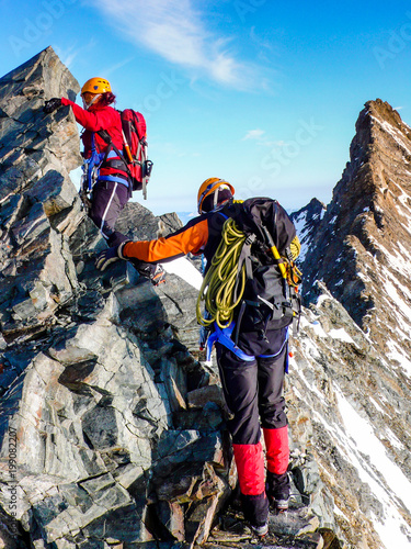 In de dag Alpinisme male and female mountain climber on an exposed rocky summit ridge on their way to a high alpine mountain peak