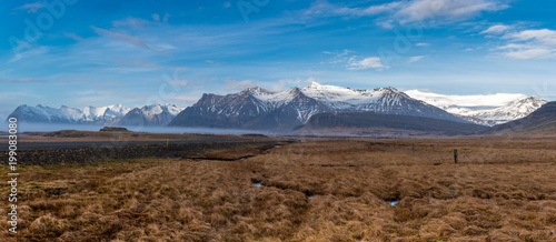 Deurstickers Canarische Eilanden Panorama of the snow capped mountains near Skalafell in Iceland with blue sky, grass, a stream, and a winding road in the foreground