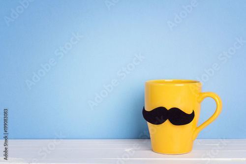 Yellow mug with a mustache on blue background. Copy space. Fathers day holiday.
