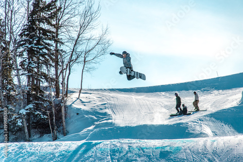 snowboarder grabbing his board in the air being watched by his friends Canvas Print