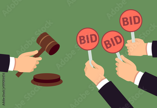 Photo Bidders human arms holding bid paddle and auctioneer hand with gavel