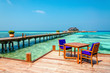 Tables and chairs in a wooden restaurant on stilts on the background of azure water and sunny sky