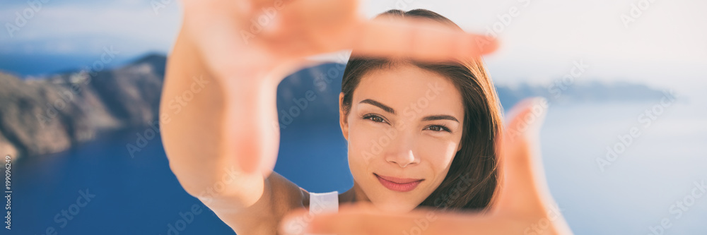 Fototapeta Beautiful young woman framing face with hands portrait banner panorama. Asian beauty Chinese Caucasian model in summer background. Europe travel vacation, luxury Santorini Greece holiday.
