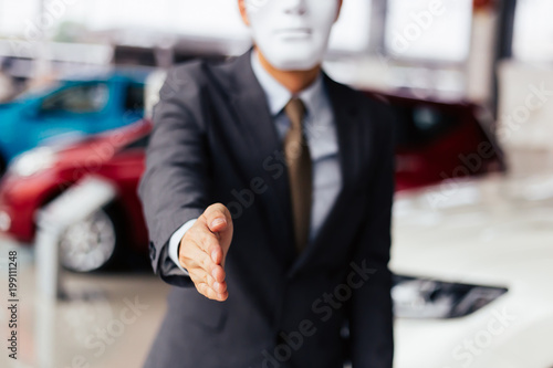 Dishonest and evil salesman in business suit in car dealership company handshaking welcome customers to exploit and deceive customers - fraud and bad quality service in business concept Fototapet