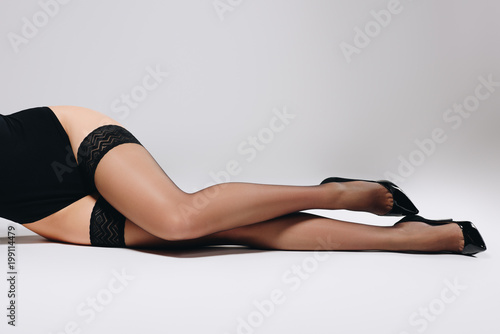 Woman in black stockings and heel shoes lying on white background Canvas-taulu