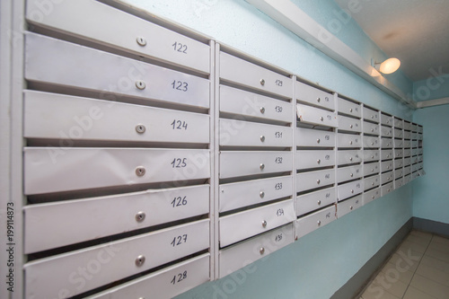 row of gray mailboxes in corridor of apartment building ...