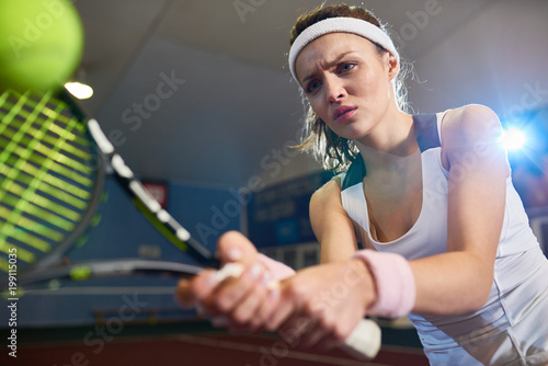 Waist Up Portrait Of Forceful Woman Playing Tennis In Indoor Court