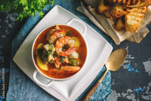 Recess Fitting Ready meals French fish soup Bouillabaisse with seafood, salmon fillet, shrimp, rich flavor, delicious dinner in a white beautiful plate.
