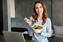 Portrait Of A Happy Young Woman Eating Fresh Salad