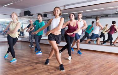 Cheerful people dancing zumba elements in dancing hall