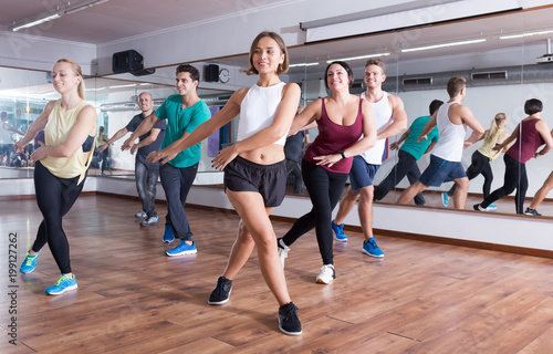 Cheerful people dancing zumba elements in dancing hall