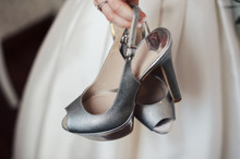 Bride Holding Silver Shoes