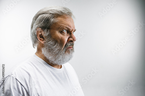Vászonkép  Senior man with disgusted expression repulsing something on white