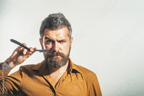 Stylish barber with dangerous razor for shaving in studio. Bearded handsome, sexy macho with straight razor in hands. Beauty industry and home skin care concept. Copy space for advertise barbershop.