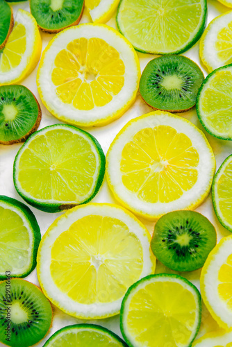Lemon, lime and kiwi sliced slices. Fruit summer refreshing background. Isolated vertical image
