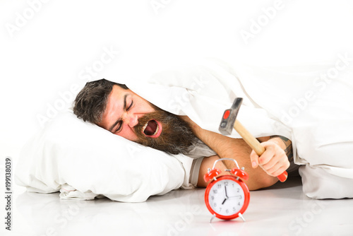 Fotografie, Obraz  Man suffers in morning, destroys alarm clock, white background.