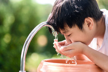 Asian Boy Take Water From Faucet To Wash His Mouth.