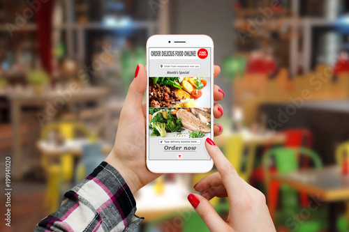 Girl ordering food with smartphone app in restaurant