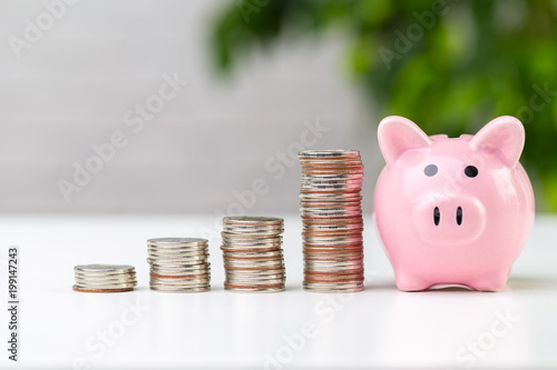 Fotografia piggy bank with coin on the table