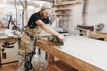 Cieśla praca z strugarki elektrycznej na drewnianej desce w warsztacie. Rzemieślnik tworzy własną, małą firmę.
