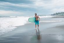 Handsome Surfer Walking With Surfboard And Looking At Ocean In Bali, Indonesia