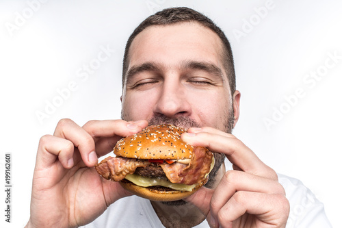 Weird and bizarre man is eating fat and juicy hamburger Fototapeta