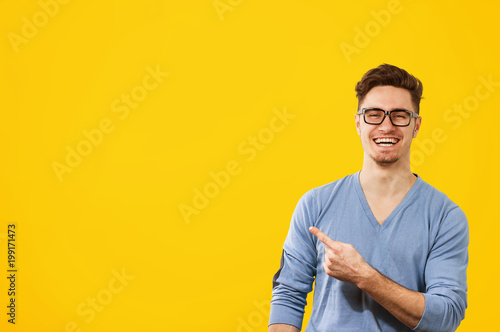 Fotomural hipster man in glasses pointing happily away on orange yellow background