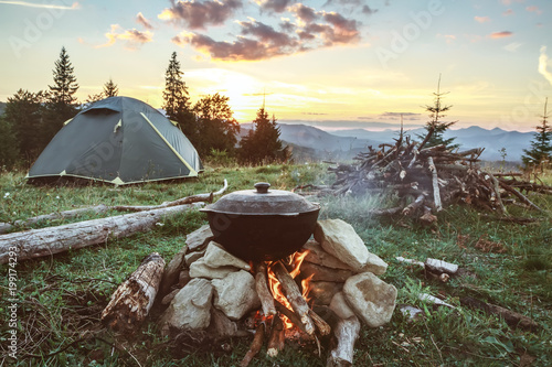 Tourist camp with fire, tent and firewood Fotobehang