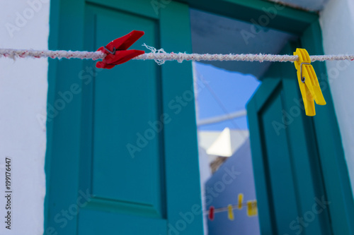 Photo A close up of colorful clothespins front of the entrance a Cycladic house