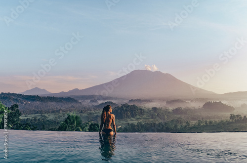 Poster Lieu connus d Asie beautiful girl staying near swimming pool with fantastic volcano Agung view