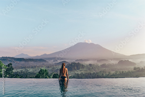 Photo sur Aluminium Bleu clair beautiful girl staying near swimming pool with fantastic volcano Agung view