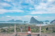 beautiful girl staying on the top of hill with fantastic panoramic view on beautiful Thai bay