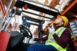 Side view portrait of young man sitting in forklift and using walkie-talkie while moving goods in warehouse, copy space