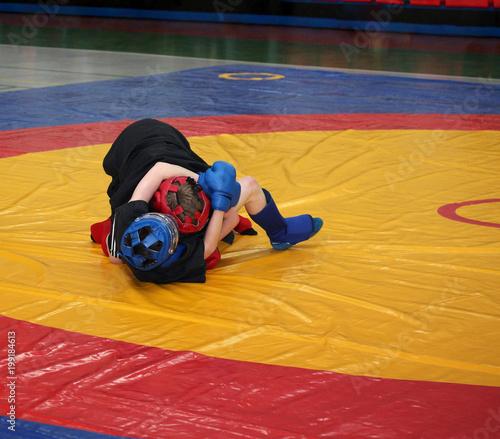 Fotografie, Obraz  Two boys are fighting on the wrestling mat