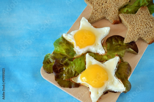 Fotografía  Fried eggs and slices of brown bread shaped as stars on a wooden board on blue b