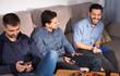 Cheerful men using phone while enjoying beer at home