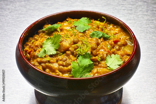 Moong Dal, indian vegetarian lentil soup in terra cotta bowl.