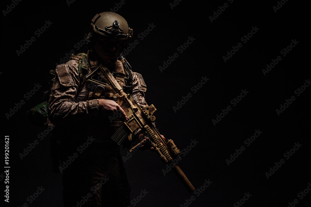 Fototapeta Special forces United States soldier or private military contractor holding rifle. Image on a black background.