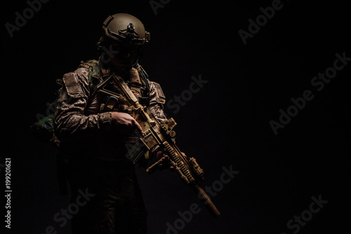 Obraz Special forces United States soldier or private military contractor holding rifle. Image on a black background. - fototapety do salonu