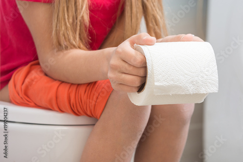 Fotografia, Obraz  A girl is holding a roll of toilet paper in her hands, sitting on the toilet