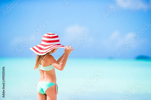 Adorable little girl in big red hat on the beach Canvas-taulu