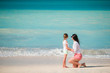 Beautiful mother and daughter on white beach
