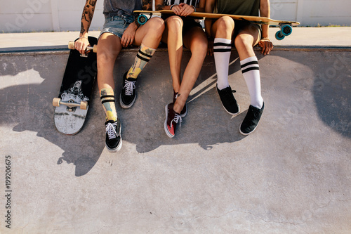 Legs of women sitting on ramp at skate park