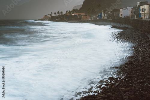 Fotografering  Long exposure foam ocean waves with blowing spray on rocky volcanic shore