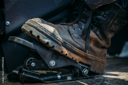 Worker foot in large shoe or boot presses on pedal of industrial excavator or tr Wallpaper Mural