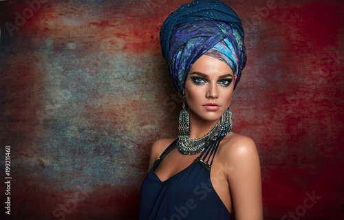 Fotomural portrait of a beautiful young tanned girl in a blue dress, a tall turban on her head and in silver jewelry on a motley background