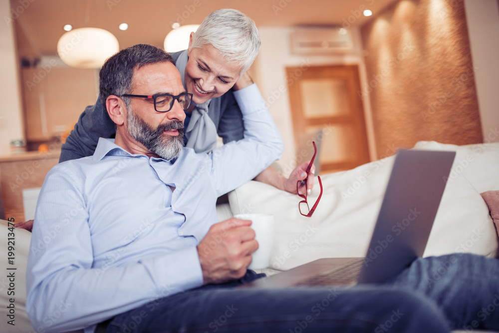 Fototapeta Mature couple using laptop computer at home