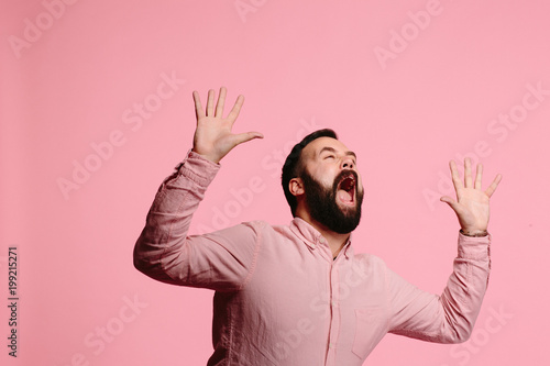 Photo  Screaming man with beard and both hands up in the air, mouth wide open, freaking